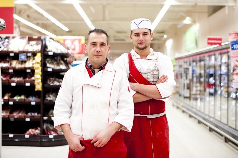 """Des bouchers sont en train de poser devant le rayon Boucherie du magasin """"Leclerc"""""""